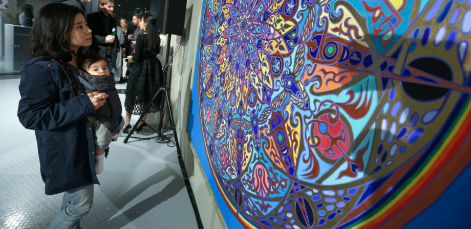 A picture of a woman and baby looking at a large mandala painting at Trinity Art Gallery in London by famous Mandala Artist Stephen Meakin 2021